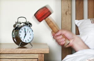 hitting alarm clock with hammer