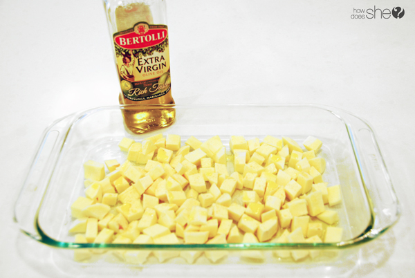 casserole dish with diced potatoes and a bottle of olive oil