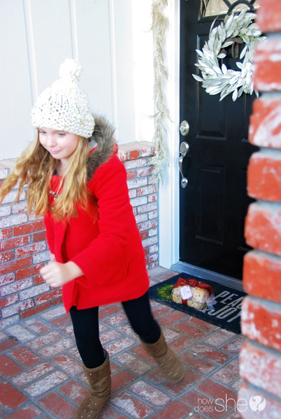 little girl leaving a Christmas treat at a door