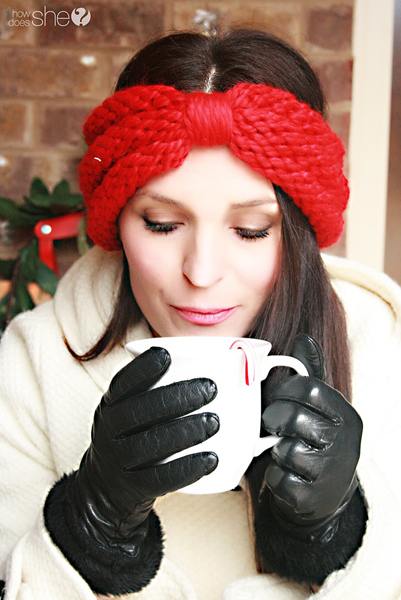 woman in headband and gloves holding a cup of hot chocolate