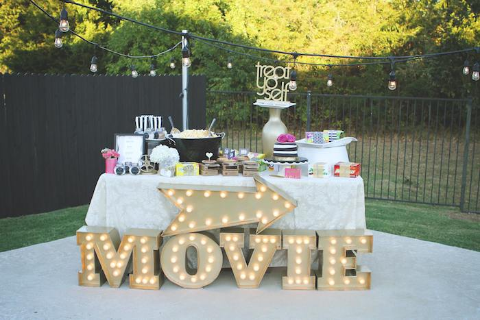 table decorated with cake and other treats for movie themed party