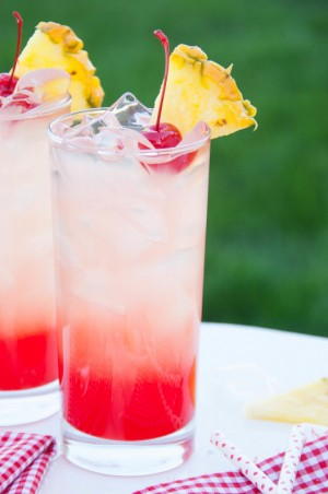 photo of two glasses of lemonade with pineapple and cherry garnishes
