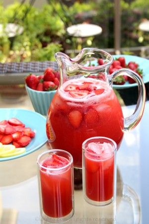 pitcher and two glasses of strawberry lemonade with strawberries in a bowl and on a plate in the background