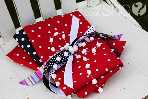 fabric Christmas bags tied with a ribbon sitting on a chair