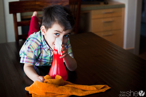 young boy holding a spray bottle using natural cleaners